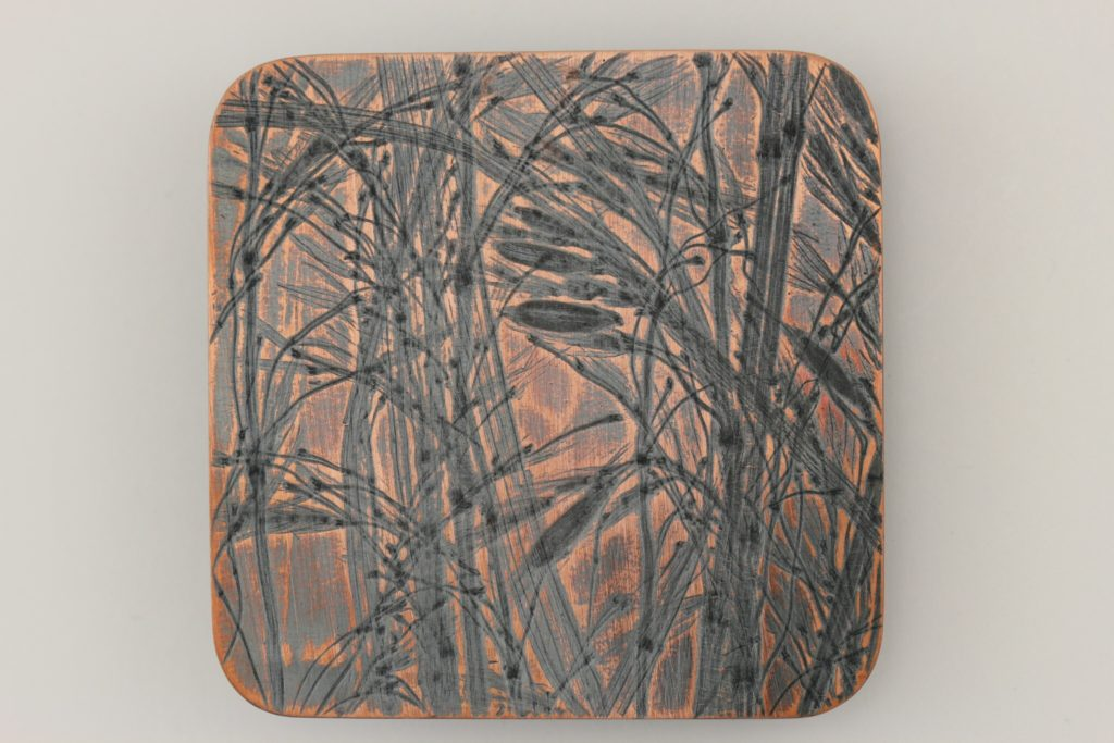 Copper belt buckle with impression of Nebraska prairie grass.
